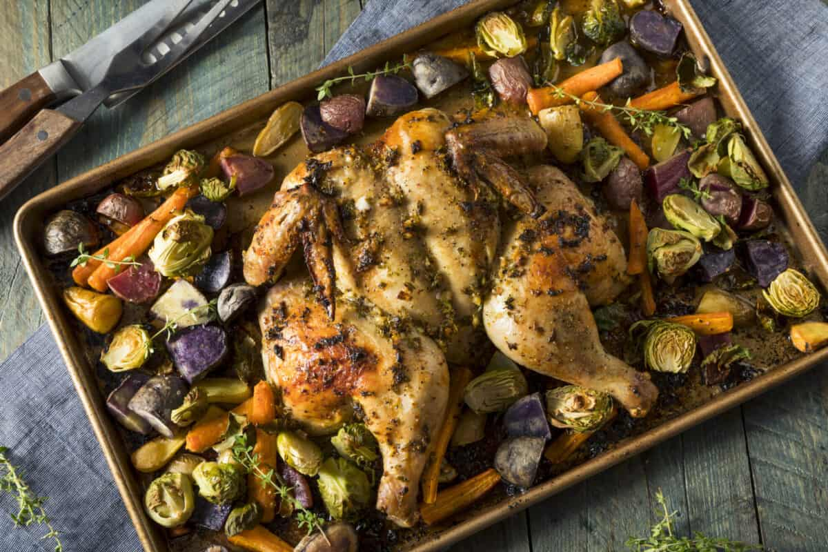 spatchcocked chicken on a baking sheet with roasted vegetables