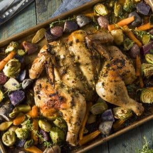 rimmed baking sheet with roast chicken and vegetables