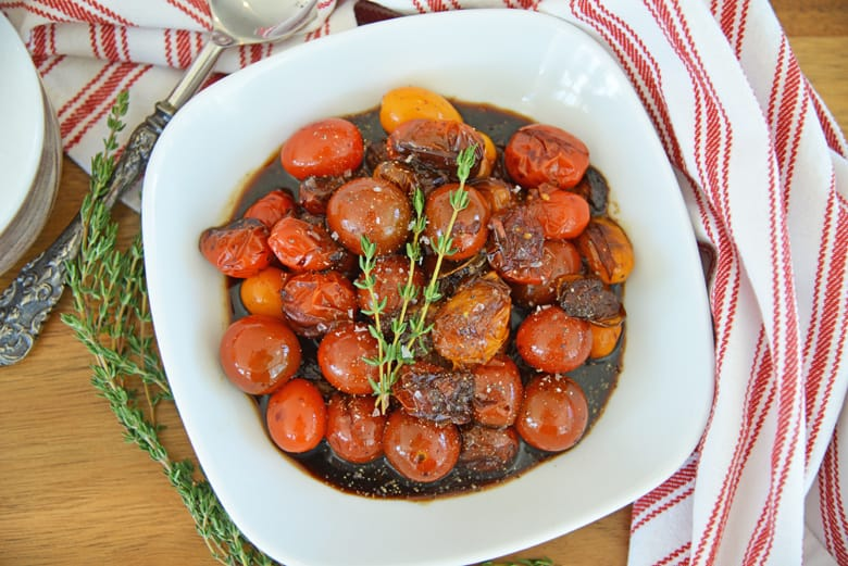 overhead of balsamic stewed tomatoes in a white serving bowl with seasoning