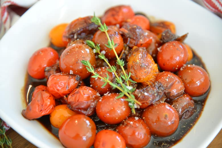 white bowl of stewed tomatoes with thyme garnish