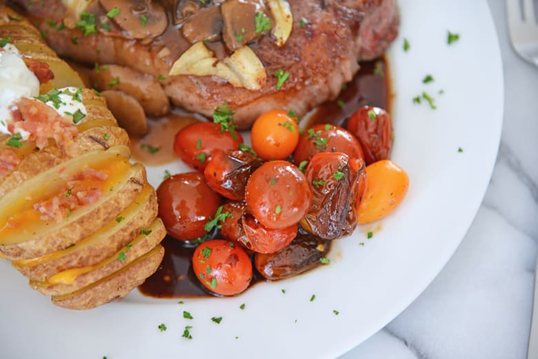 stewed tomatoes served with potatoes and steak