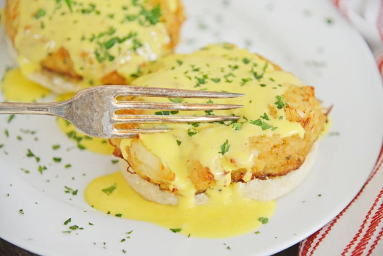 fork cutting into crab cakes hollandaise
