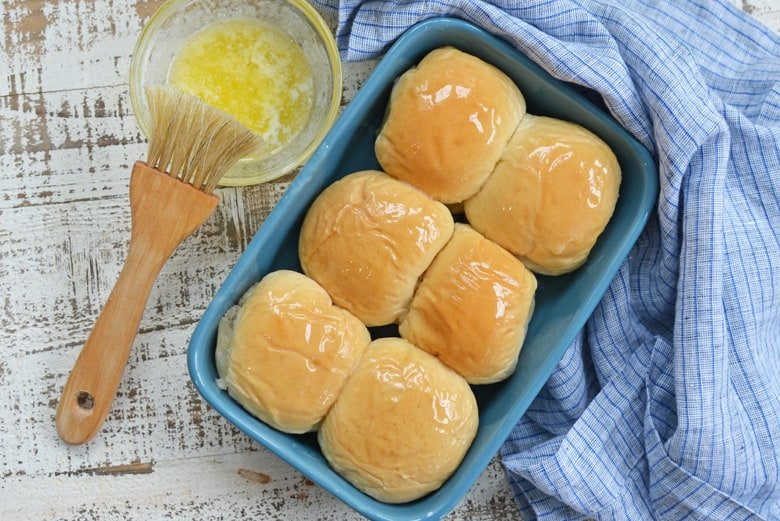 buttered dinner rolls in a blue baking dish