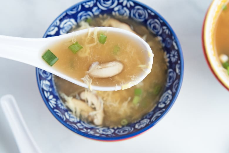 spoon of egg drop soup with mushroom and scallion