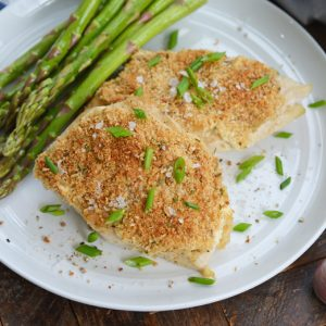 garlic parmesan chicken on a white plate with asparagus
