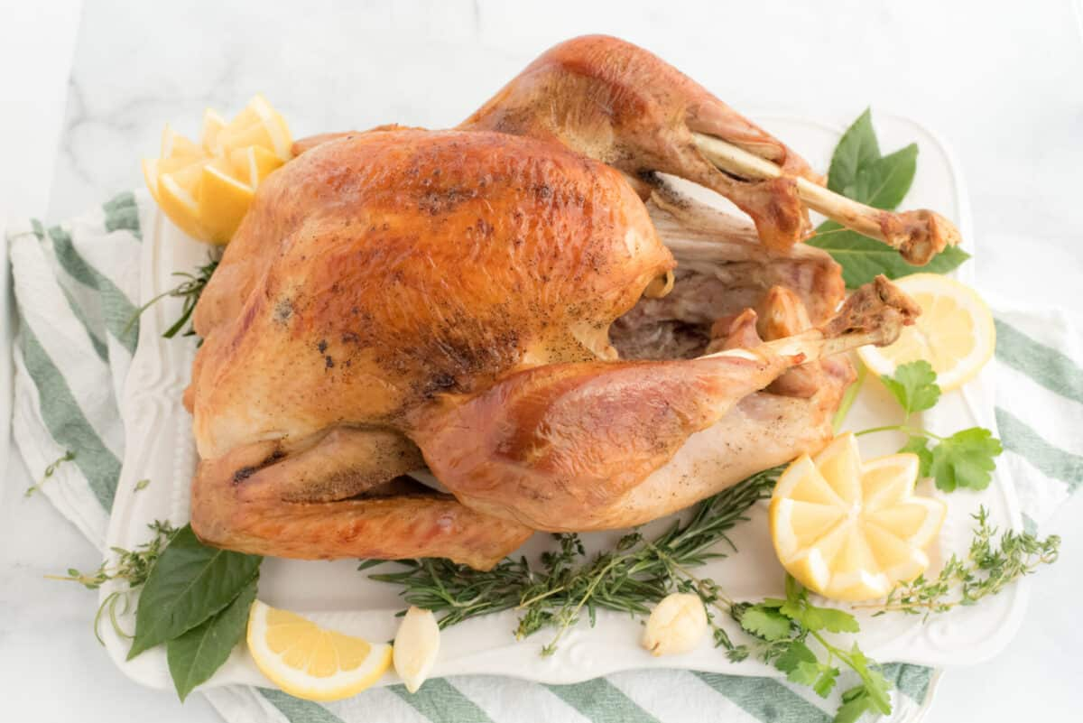 whole turkey on a serving platter with lemons and fresh herbs