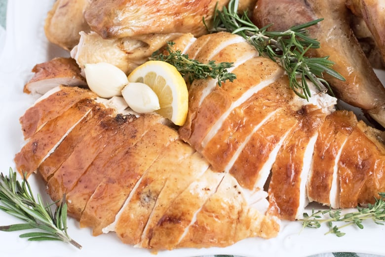 close up of carved turkey breast with herbs and lemon