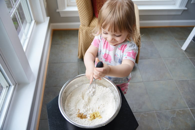 little girl mixing bread dough