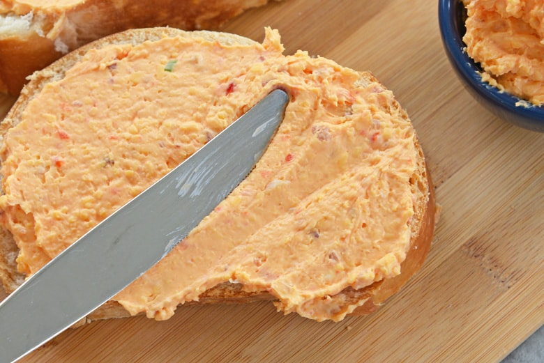 pimento cheese spreading onto a piece of bread