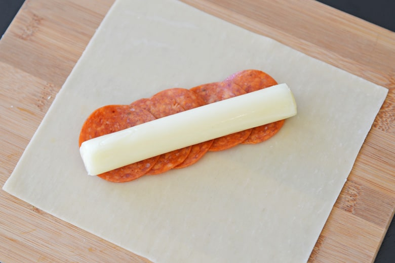 pepperoni and cheese on an egg roll wrapper