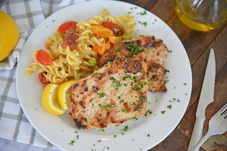 grilled chicken on a white plate with pasta salad
