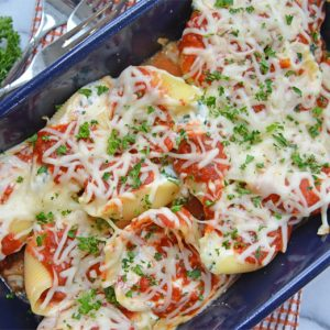 spinach stuffed shells in a blue casserole dish