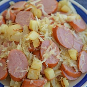 sauerkraut and sausage on a blue and white serving platter