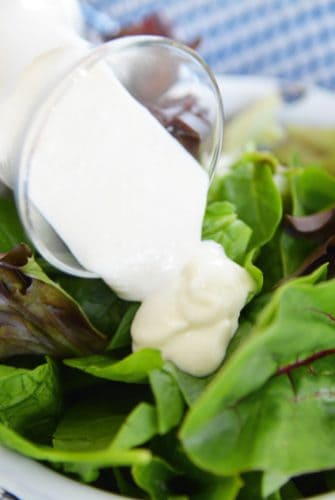 blue cheese dressing pouring over greens