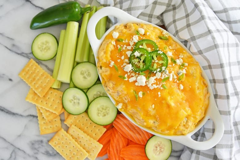 jalapeno buffalo dip with cucumbers, carrots and celery on a marble counter