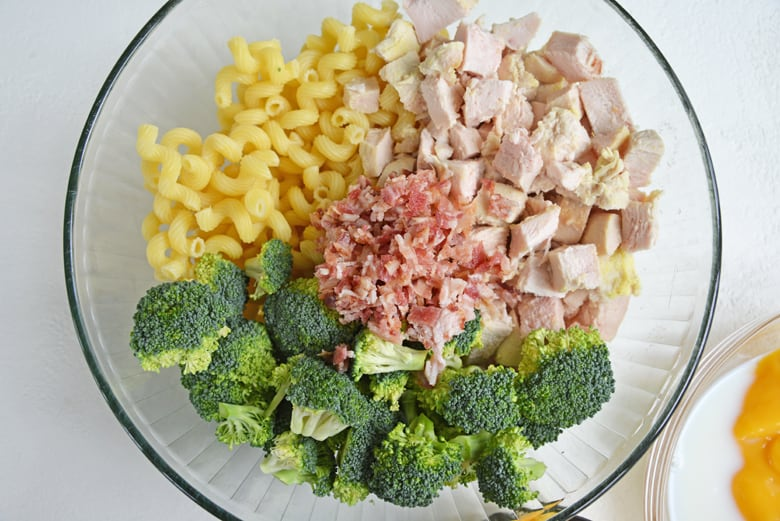 pasta, chicken, bacon and broccoli in a glass mixing bowl