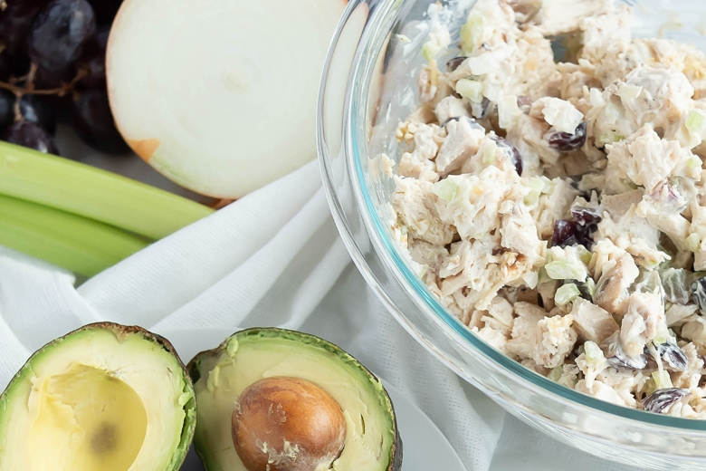 chicken salad in a mixing bowl with avocado halves
