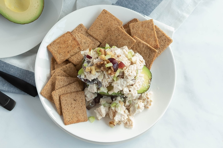 chicken salad avocados with multigrain chips on a white plate