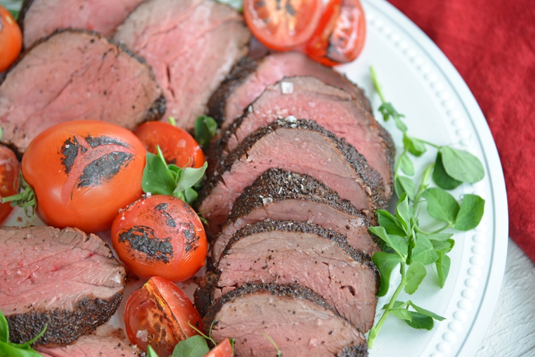 close up of sliced coffee crusted beef tenderloin with pea shoots and tomatoes