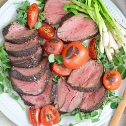 plate of seared beef tenderloin with tomatoes and scallions