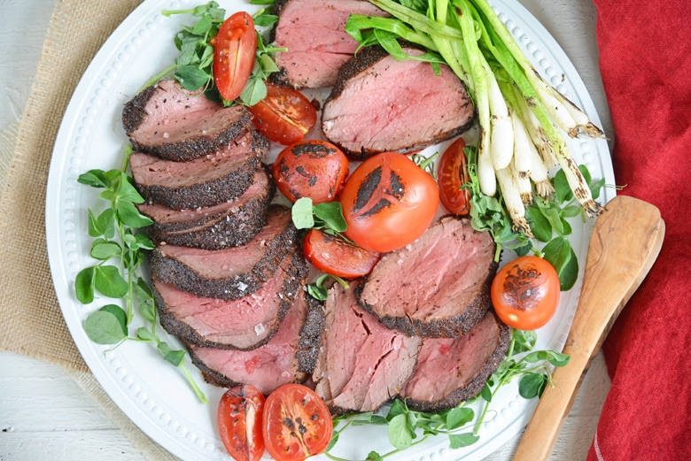 overhead view of plated kona crusted beef tenderloin with tomatoes, pea shoots and scallions