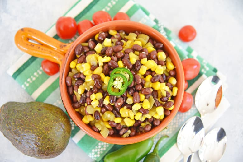 overhead og black bean corn salad in a orange serving bowl with avocado and tomatoes