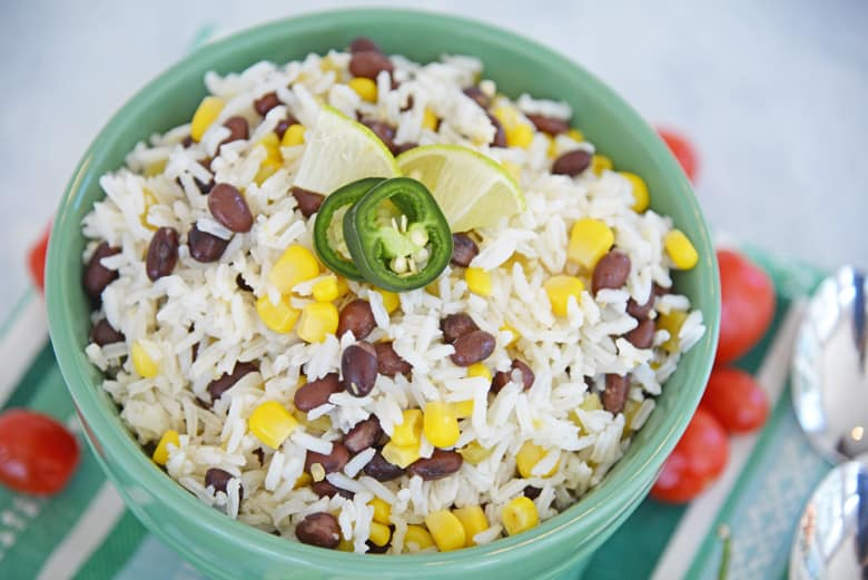 white rice with beans, corn, jalapeno and lime wedges in a green serving bowl