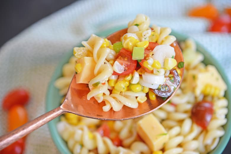 gouda and corn pasta salad in a serving spoon