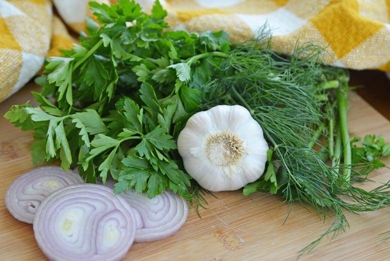 parsley, cilantro, dill, garlic and shallot on a cutting board