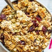 A bowl of food on a plate, with Granola