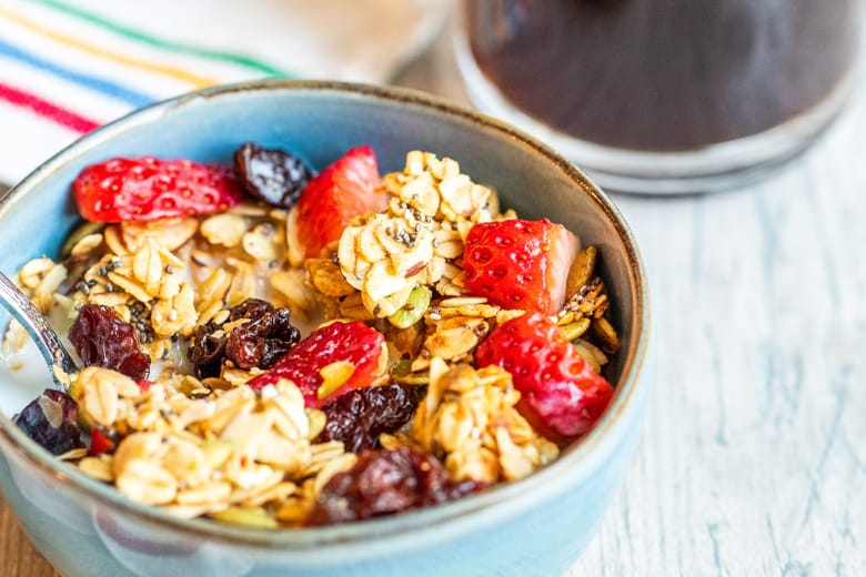 granola in a blue bowl with fresh berries
