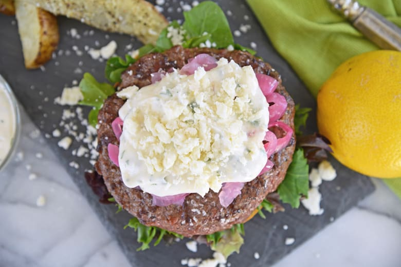 overhead of greek lamb burger with toppings on slate plate