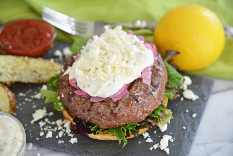 serving greek burgers with lemon and potato wedges