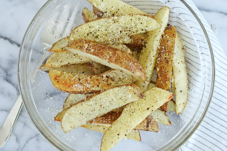 parmesan garlic potato wedges in a glass mixing bowl