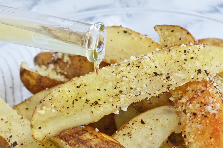 truffle oil pouring over baked potato wedges