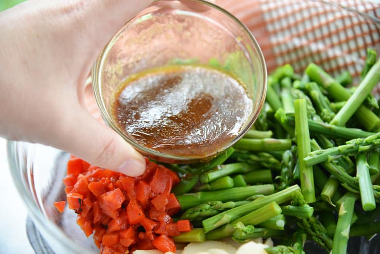 pouring balsamic vinegar dressing on marinated asparagus
