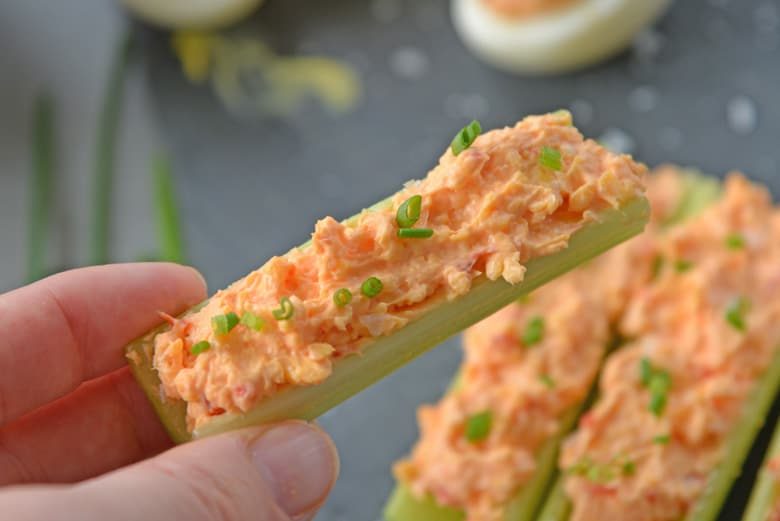 hand holding a pimento cheese celery stick