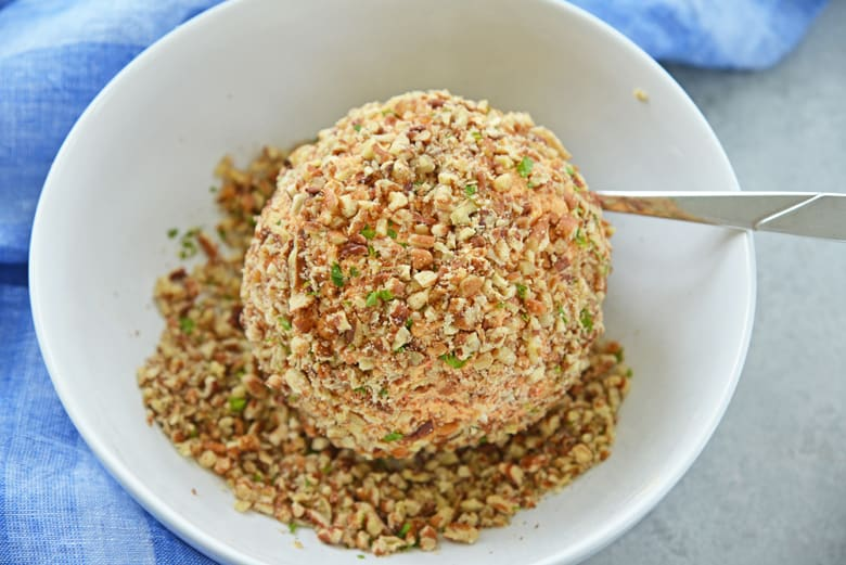 pimento cheese ball in a bowl of chopped walnuts