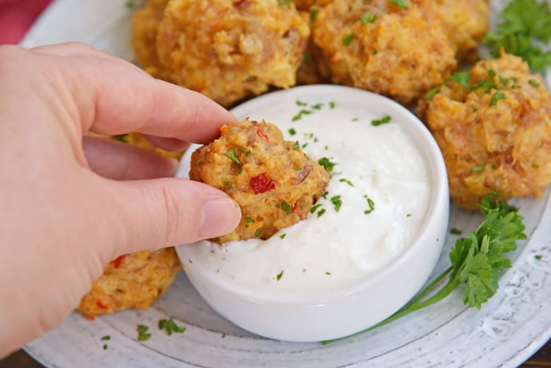dipping a pimento sausage ball in aioli sauce