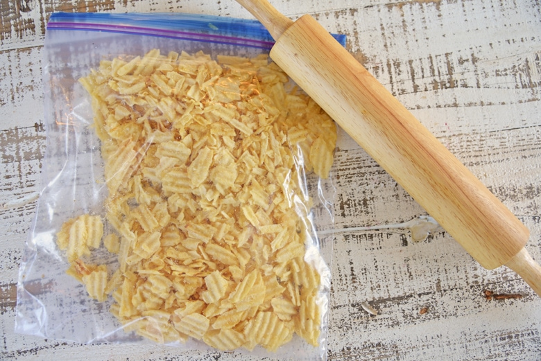 wavy potato chips in a plastic bag with a rolling pin
