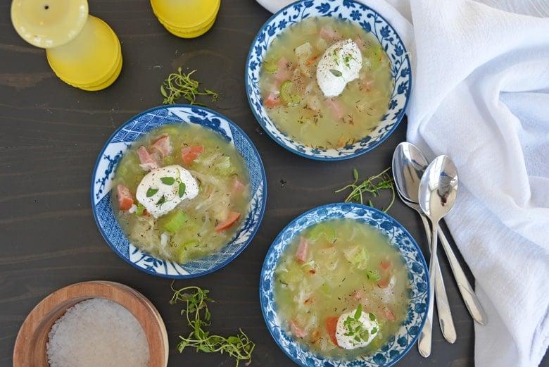three bowls of pork and sauerkraut soup with garnishes