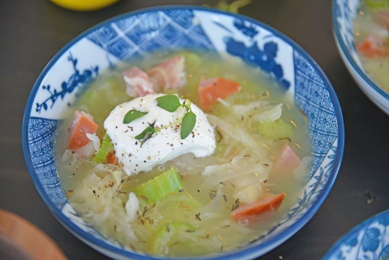 angle view of sauerkraut and kielbasa soup with sour cream and thyme garnish