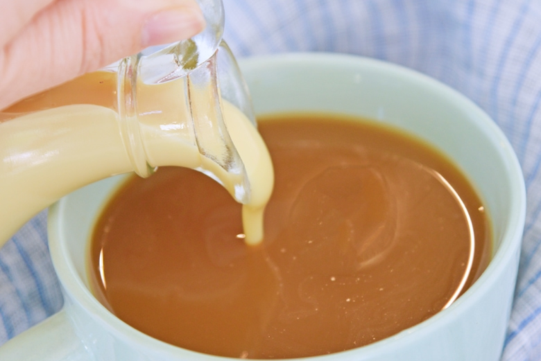 sweetened condensed milk pouring into a cup of coffee