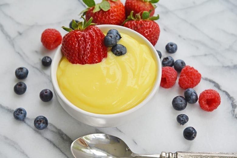 bowl of old fashioned vanilla custard on marble countertop with fresh berries