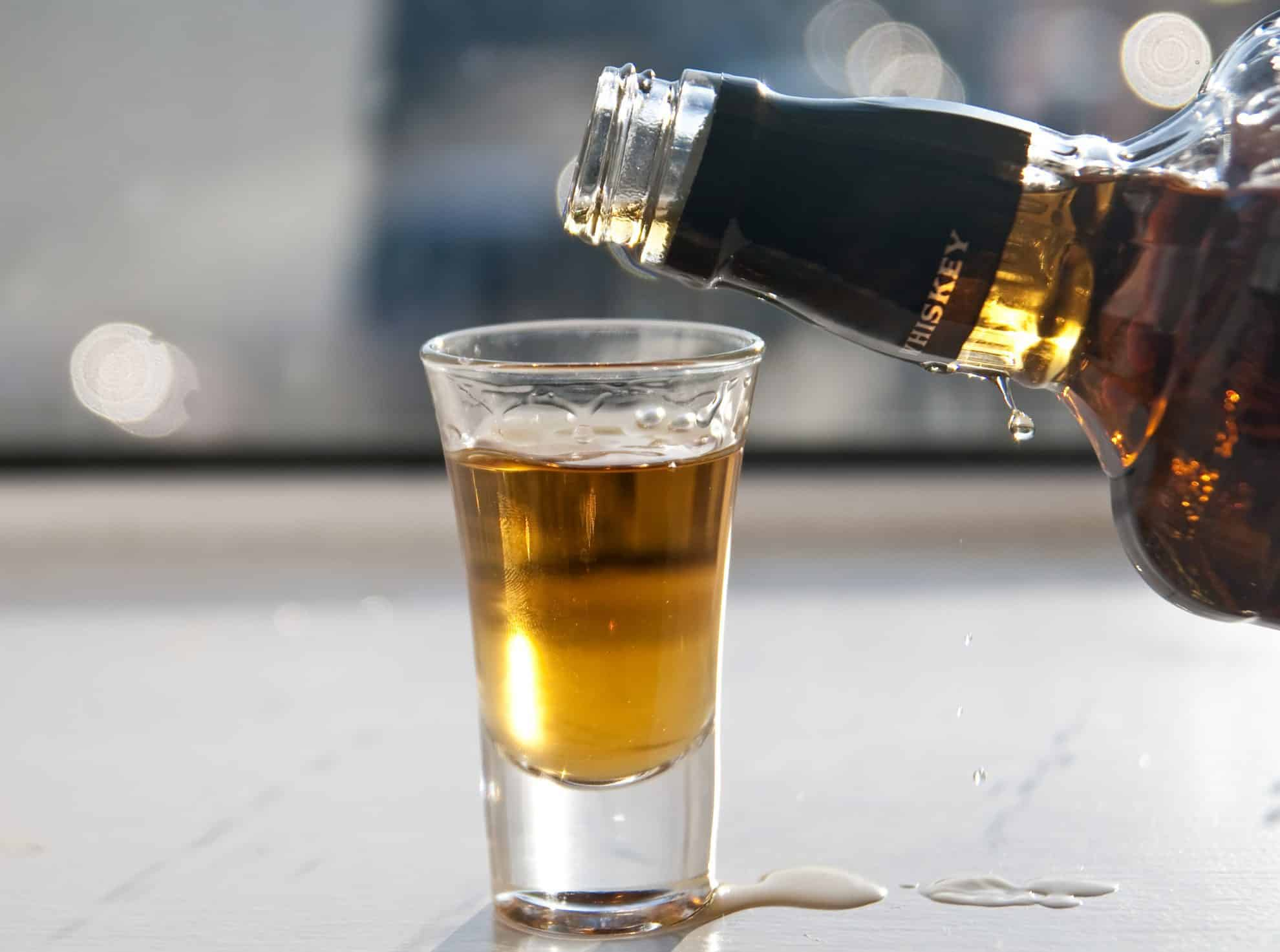 whiskey pouring into a shot glass
