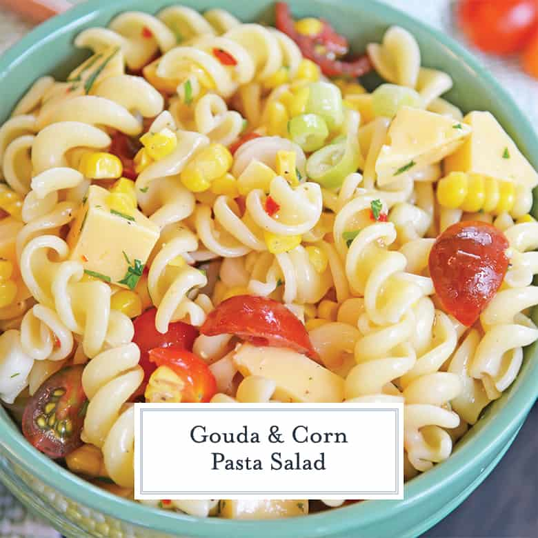 close up of corn pasta salad in a teal bowl