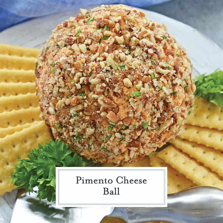 Pimento cheese ball covered in pecans and parsley with club crackers