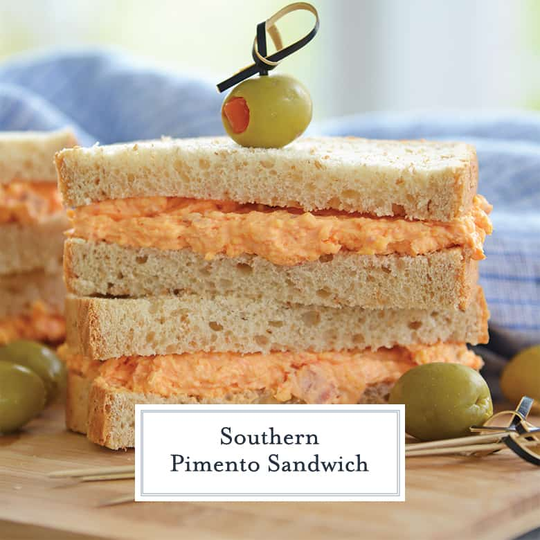 Sliced pimento cheese sandwich stacked with a toothpick and olive