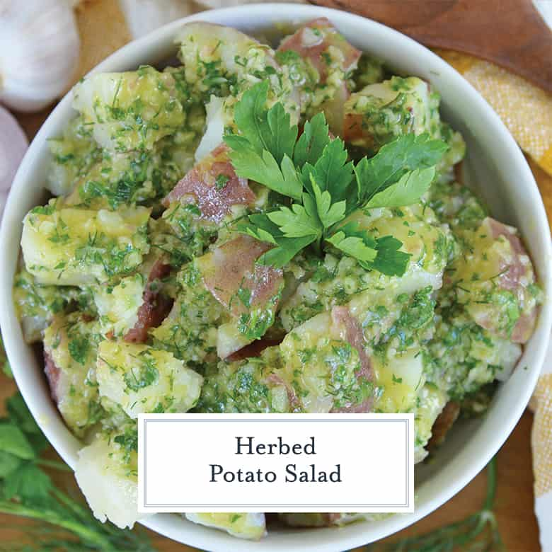 Overhead view of cold potato salad in a white bowl garnished with parsley