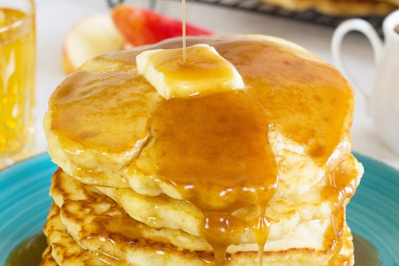 close up of pancakes with apple syrup pouring over them